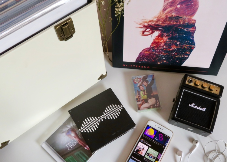 Various albums on a flat surface next to an iPhone 8, Marshall speaker, and a pair of headphones