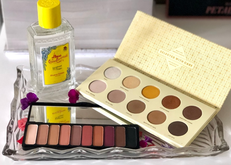 Two eyeshadow palettes and a perfume on a glass tray