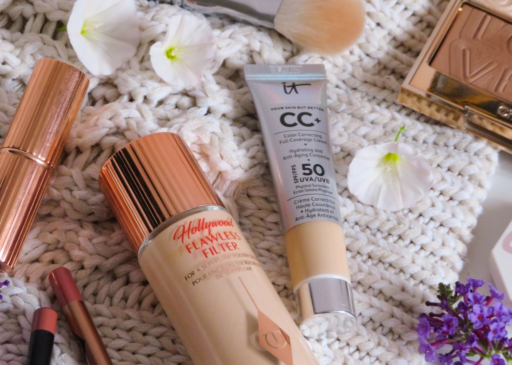 Makeup products surrounded by flowers on a white jumper