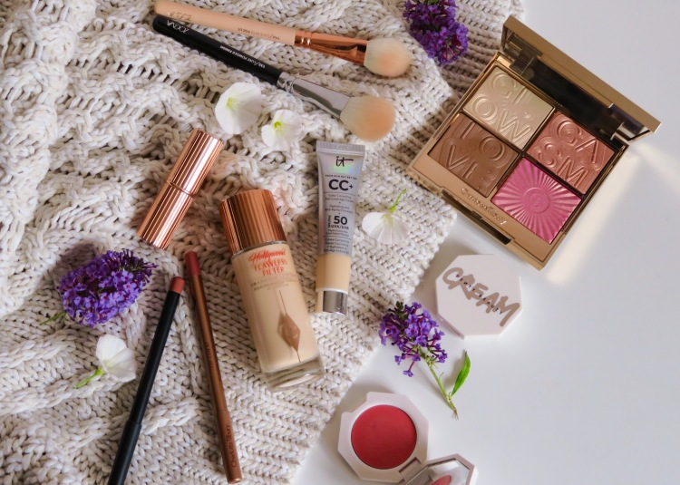 Makeup products lying on a white background, including Charlotte Tilbury, Fenty Beauty, It Cosmetics and Zoeva